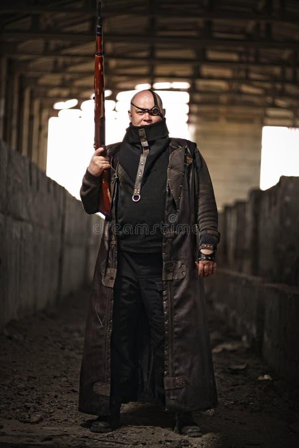 Retrato de un hombre calvo del mundo posts-apocalíptico con el rifle en la ropa de cuero como el polvillo radiactivo del estilo o imagen de archivo libre de regalías