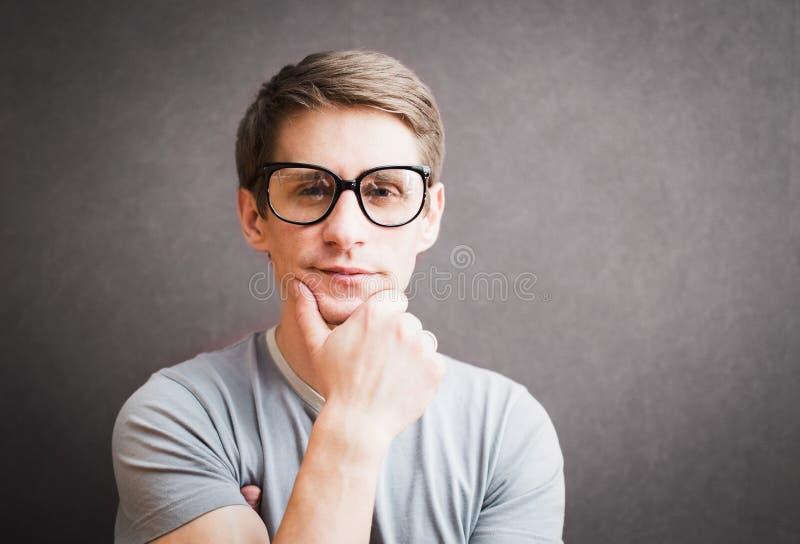 Retrato de un hombre con las lentes que se oponen a la pared gris, h foto de archivo