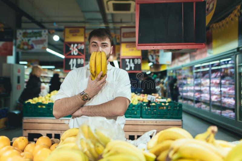 Retrato de un hombre con los plátanos alrededor de su cara mientras que hace compras en un supermercado fotografía de archivo libre de regalías