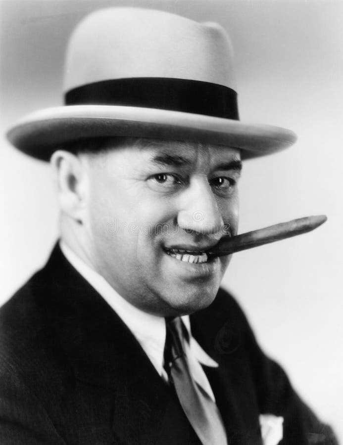 Retrato de un hombre con un sombrero y un cigarro en su boca (todas las personas representadas no son vivas más largo y ningún es foto de archivo libre de regalías