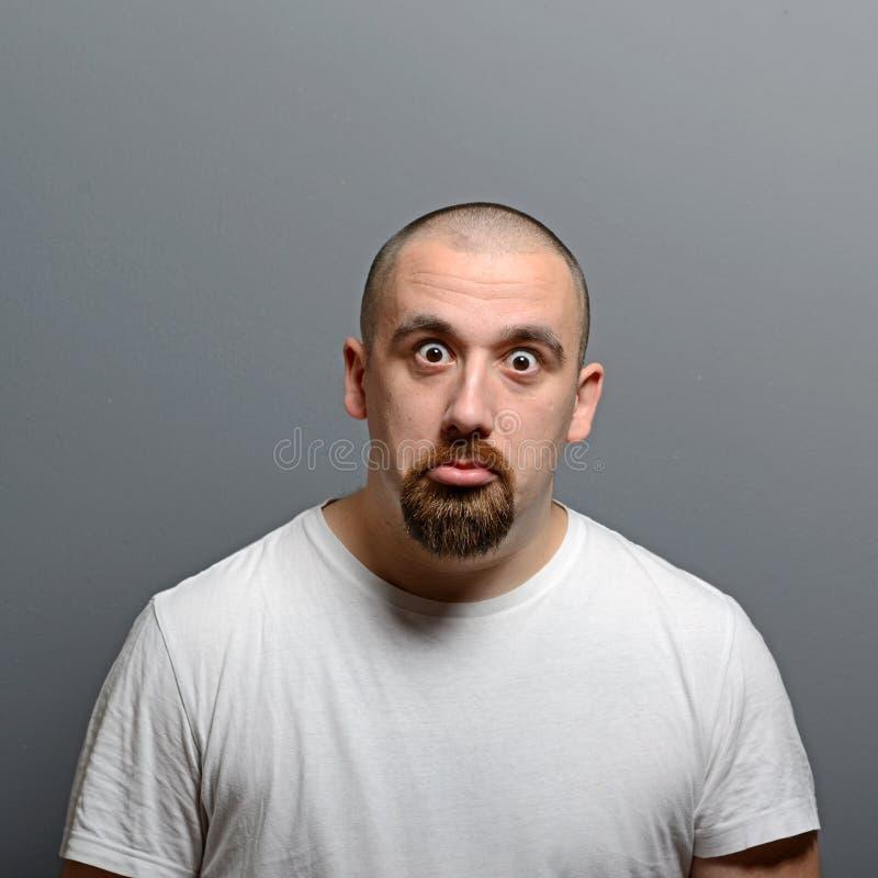 Retrato de un hombre confuso contra fondo gris imagen de archivo libre de regalías
