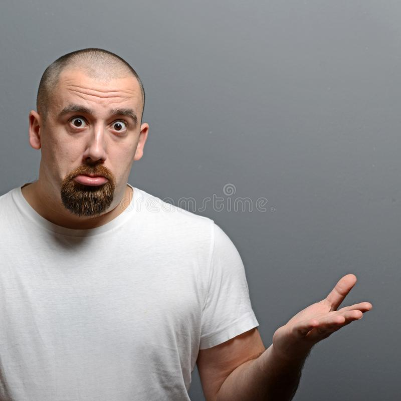 Retrato de un hombre confuso contra fondo gris imágenes de archivo libres de regalías