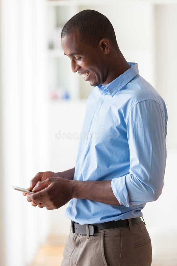 Retrato de un hombre de negocios afroamericano joven que usa un móvil fotografía de archivo