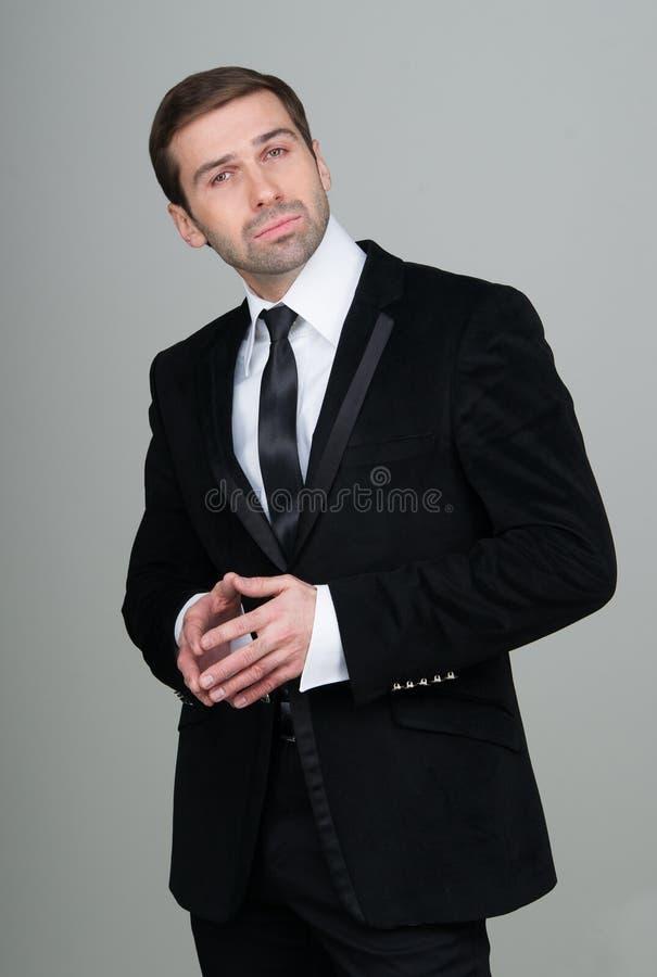 Retrato de un hombre de negocios confiado y acertado en traje negro fotos de archivo