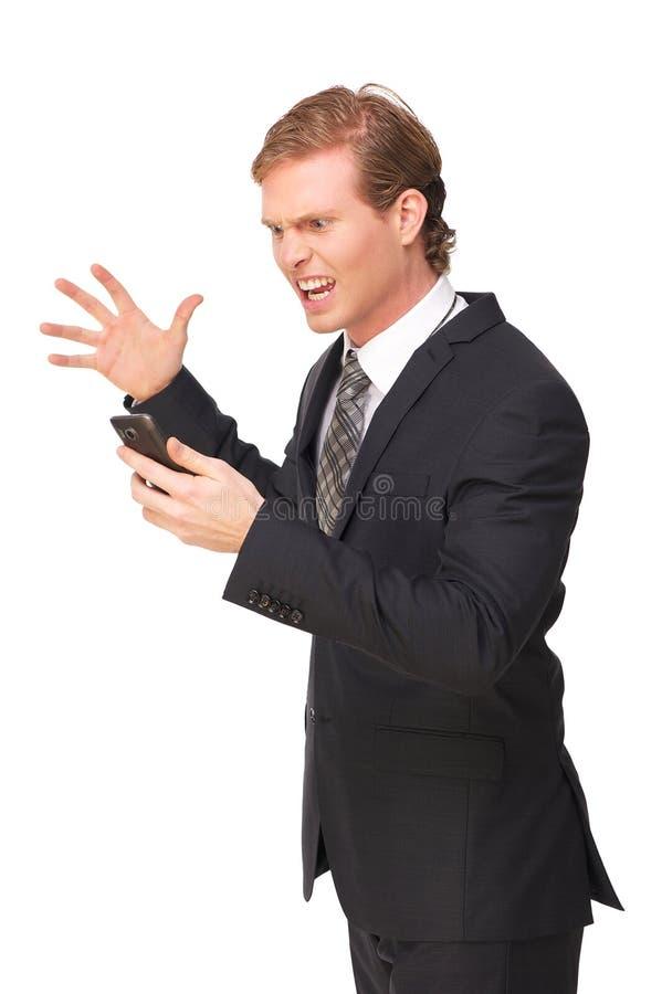 Hombre de negocios frustrado que mira el teléfono foto de archivo