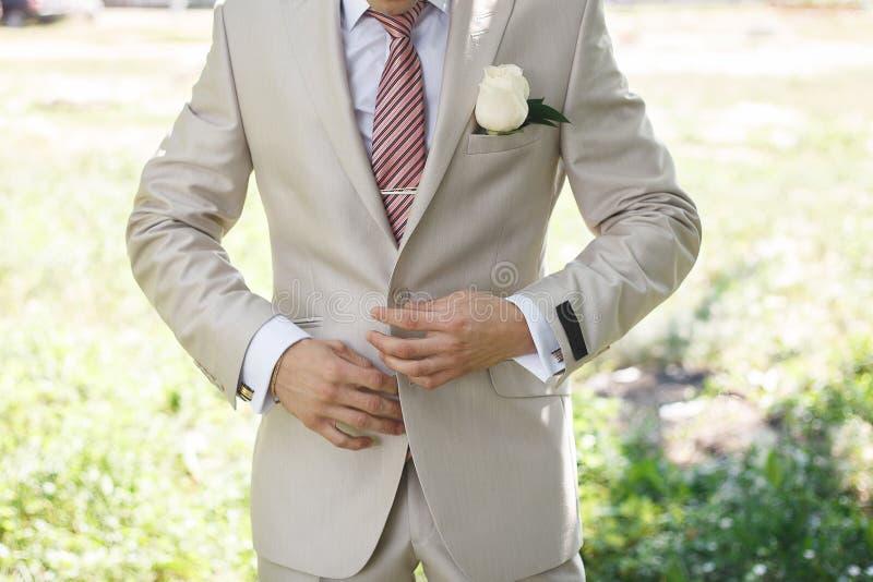 Retrato de un hombre de negocios joven atractivo o novio en traje blanco que lleva del fondo urbano imágenes de archivo libres de regalías