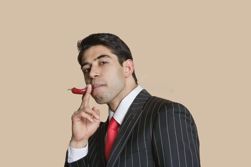 Retrato de un hombre de negocios joven con pimienta de chile rojo que imita como cigarrillo que fuma foto de archivo