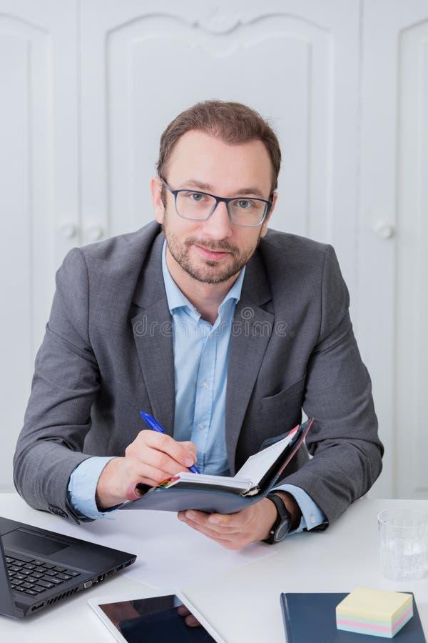 Retrato de un hombre de negocios joven en el escritorio de oficina imagen de archivo