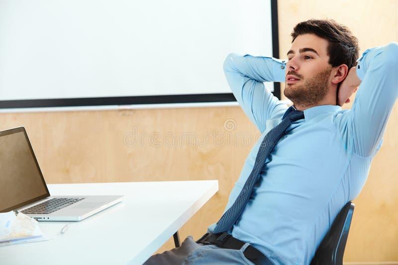 Retrato de un hombre de negocios joven relajado que se sienta en una oficina brillante imagen de archivo