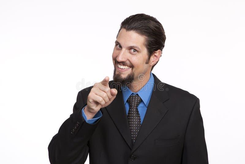 Retrato de un hombre de negocios joven sonriente que señala hacia cámara fotos de archivo