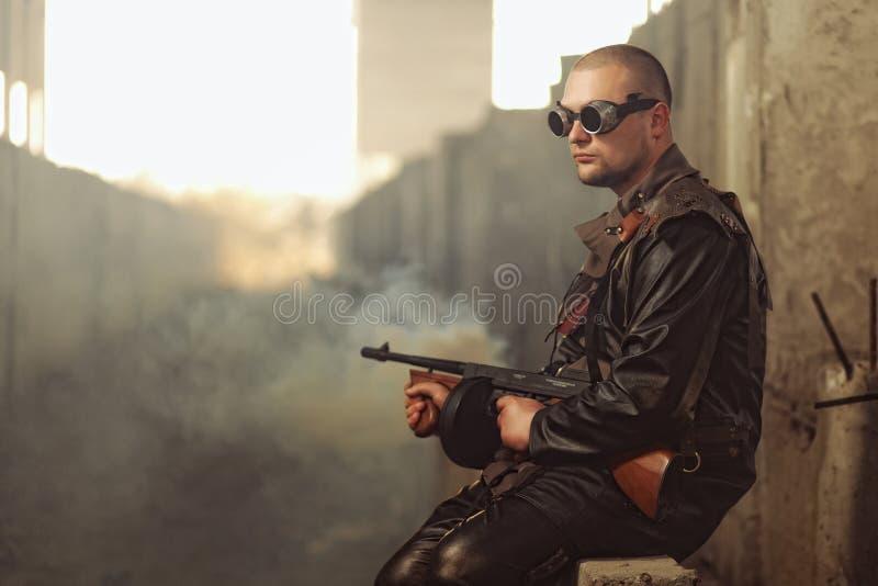 Retrato de un hombre del mundo posts-apocalíptico con la ametralladora y los vidrios negros en un edificio abandonado imagen de archivo