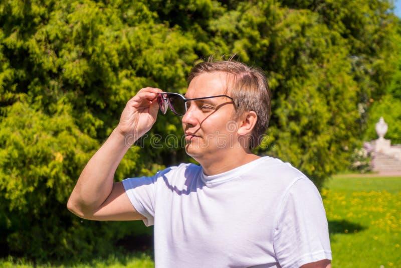Retrato de un hombre en gafas de sol y de una situaci?n blanca de la camiseta exterior en parque foto de archivo
