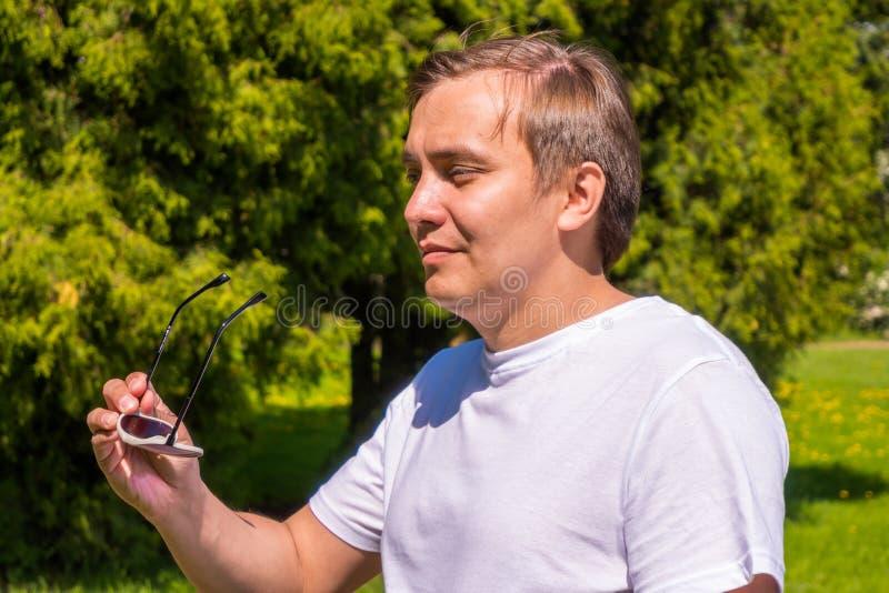Retrato de un hombre en gafas de sol y de una situaci?n blanca de la camiseta exterior en parque imagenes de archivo