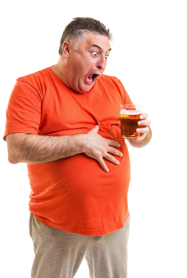 Retrato de un hombre gordo sediento que mira fijamente un vidrio de cerveza foto de archivo libre de regalías