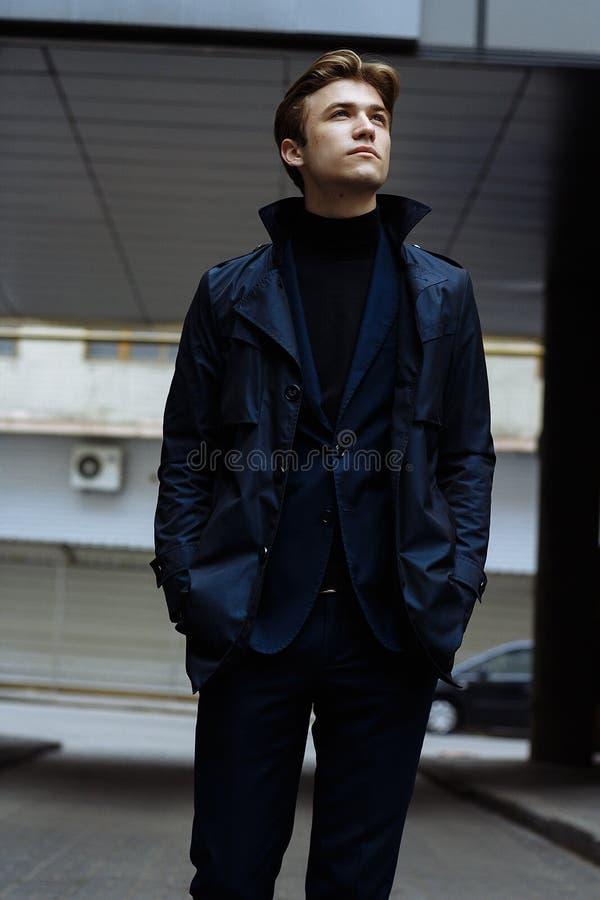 Retrato de un hombre hermoso, atractivo, joven en un traje azul, capa, en la ciudad pensativo y triste, esperando imágenes de archivo libres de regalías