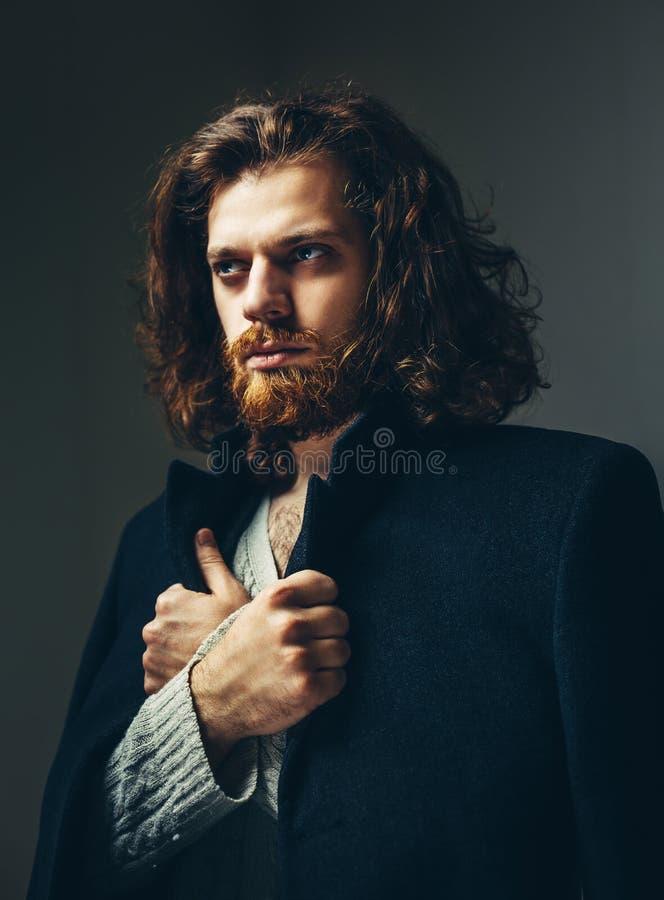 Retrato de un hombre hermoso con una barba y del pelo largo en una capa negra imagenes de archivo