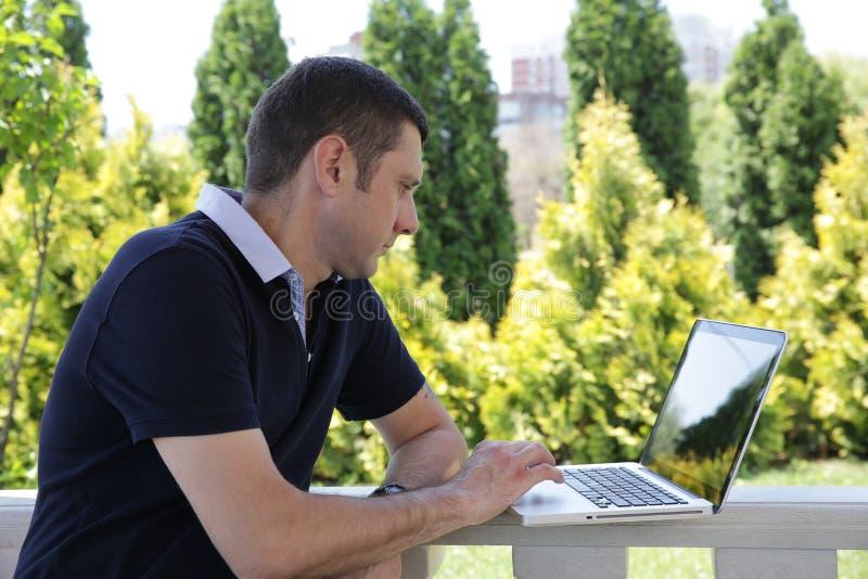 Retrato de un hombre hermoso joven con un ordenador portátil abierto en el parque foto de archivo