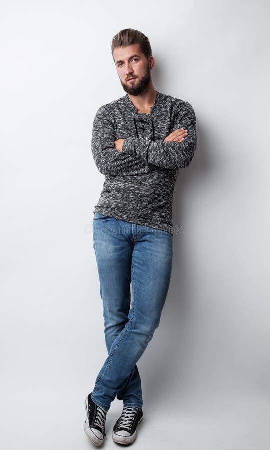Retrato de un hombre hermoso joven que se inclina contra una pared blanca imagen de archivo libre de regalías