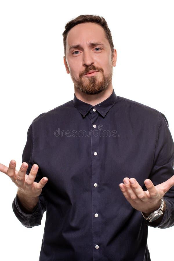 Retrato de un hombre hermoso, sin afeitar, vestido en una camisa azul marino, oponiéndose a un fondo blanco Seguro de sí mismo imágenes de archivo libres de regalías