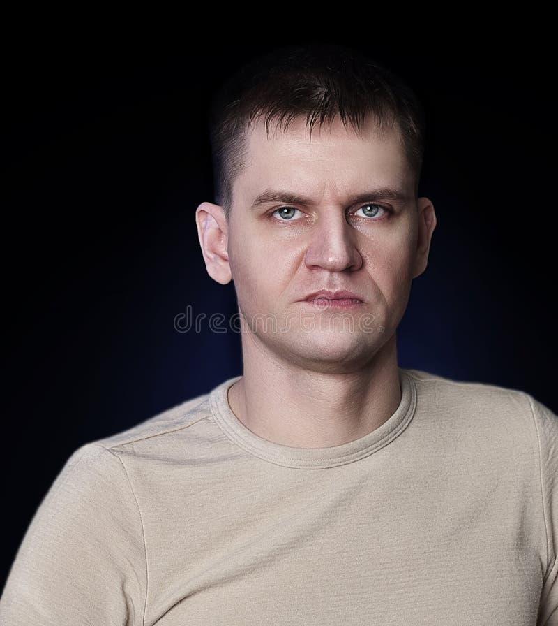 Retrato de un hombre de hombres blanco en un fondo negro en una camisa ligera fotografía de archivo