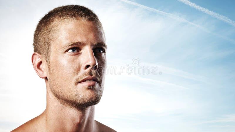 Retrato de un hombre joven atractivo en fondo del cielo azul foto de archivo libre de regalías