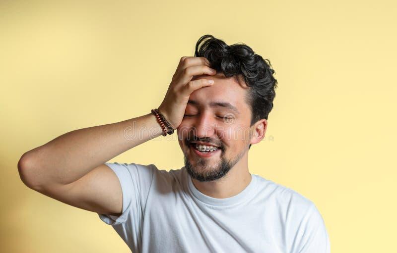 Retrato de un hombre joven con la sonrisa de los apoyos Un hombre joven feliz con los apoyos en un fondo amarillo imagenes de archivo