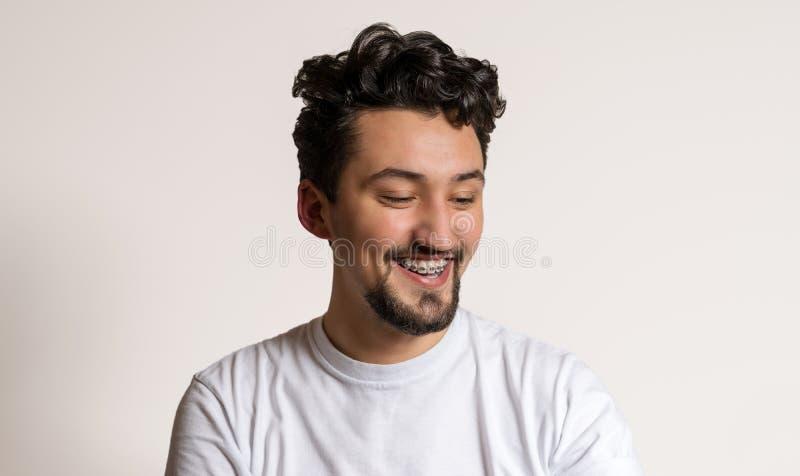 Retrato de un hombre joven con la sonrisa de los apoyos Un hombre joven feliz con los apoyos en un fondo blanco imágenes de archivo libres de regalías