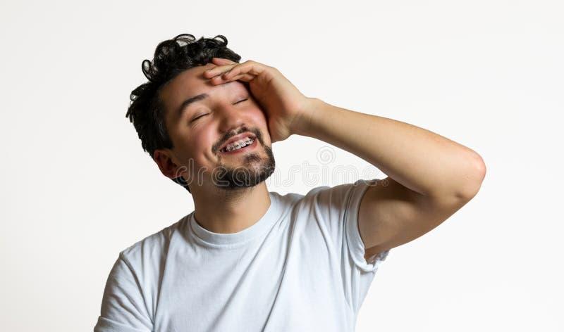 Retrato de un hombre joven con la sonrisa de los apoyos Un hombre joven feliz con los apoyos en un fondo blanco imagen de archivo