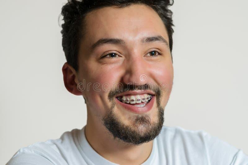Retrato de un hombre joven con los apoyos que sonr?e y que r?e Un hombre joven feliz con los apoyos en un fondo blanco fotografía de archivo
