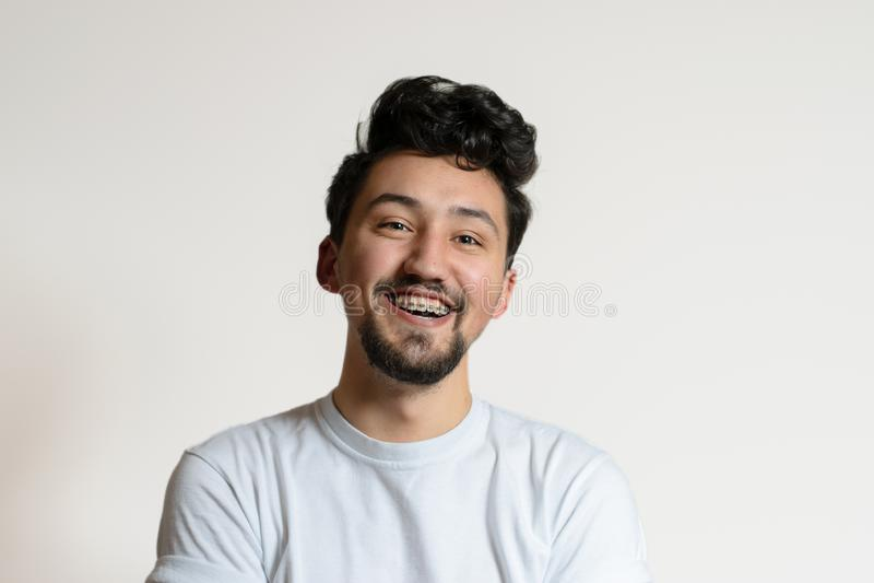 Retrato de un hombre joven con los apoyos que sonr?e y que r?e Un hombre joven feliz con los apoyos en un fondo blanco fotos de archivo