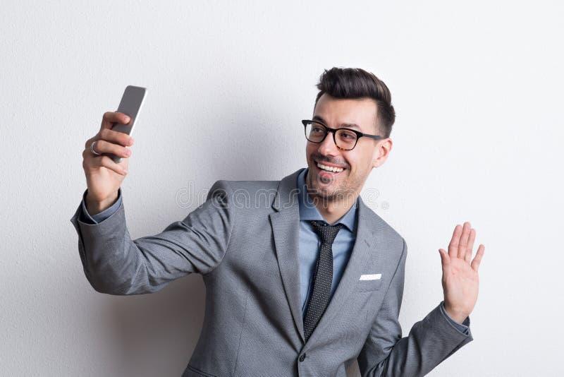 Retrato de un hombre joven con smartphone en un estudio, tomando el selfie fotografía de archivo libre de regalías