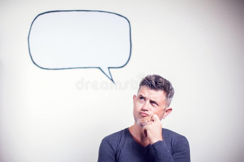 Retrato de un hombre joven con una burbuja vacía del discurso sobre su cabeza imagenes de archivo