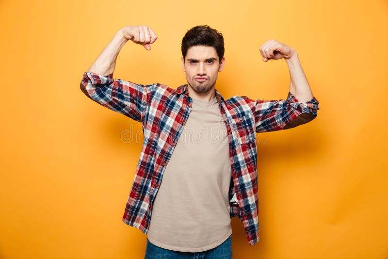 Retrato de un hombre joven confiado que dobla los músculos foto de archivo libre de regalías