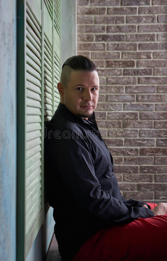 Retrato de un hombre joven, de una camisa negra y de holguras rojas, peinado w fotografía de archivo libre de regalías