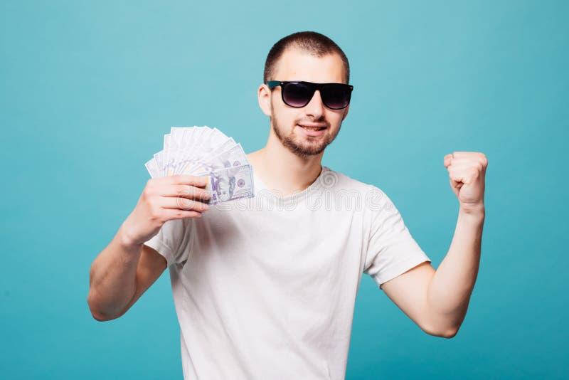 Retrato de un hombre joven del verano en gafas de sol en el éxito blanco de la camiseta que sostiene el dinero del efectivo mient imagenes de archivo