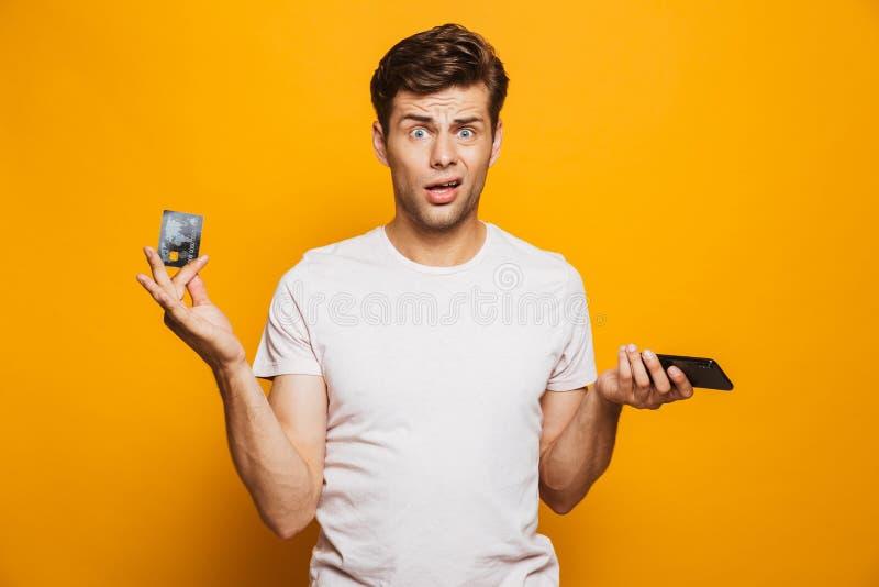 Retrato de un hombre joven desconcertado que sostiene el teléfono móvil imagenes de archivo