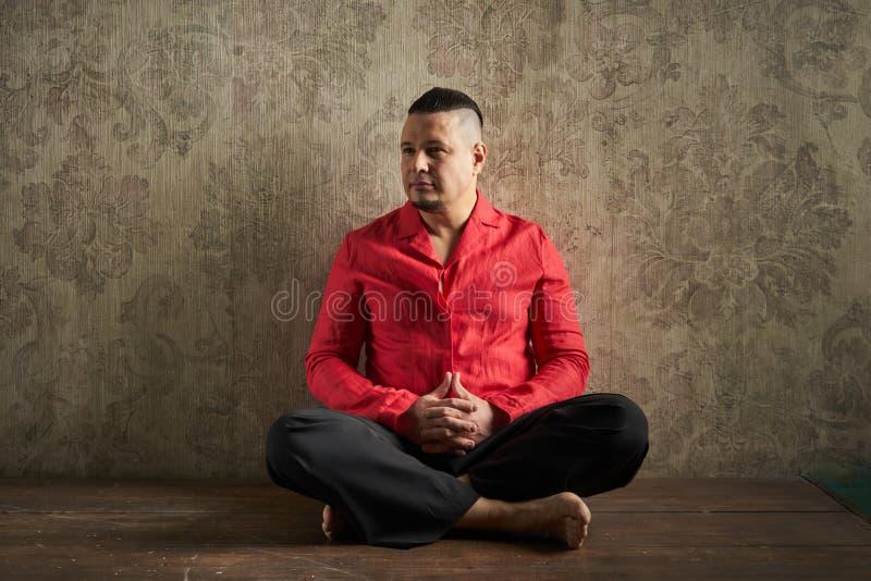 Retrato de un hombre joven, en camisa roja y holguras negras, hairstyl imagen de archivo libre de regalías