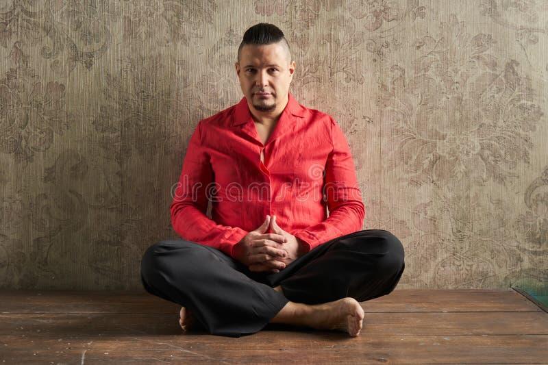Retrato de un hombre joven, en camisa roja y holguras negras, hairstyl fotografía de archivo libre de regalías