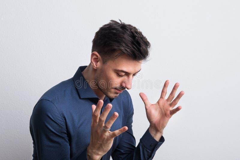 Retrato de un hombre joven en un estudio con las manos para arriba imagenes de archivo