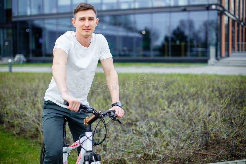 Retrato de un hombre joven en una bicicleta en la ciudad imagen de archivo libre de regalías