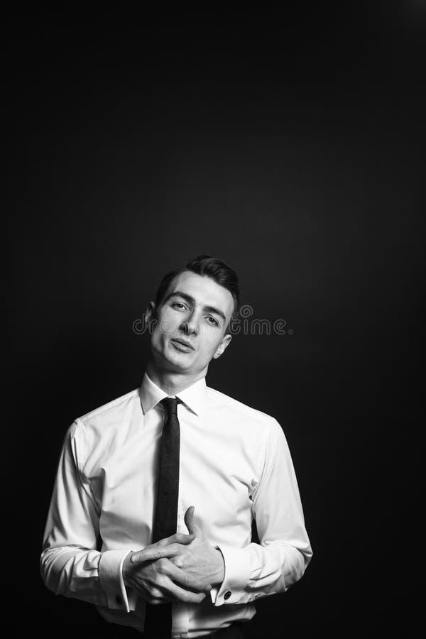 Retrato de un hombre joven en una camisa blanca y un lazo negro imagen de archivo libre de regalías