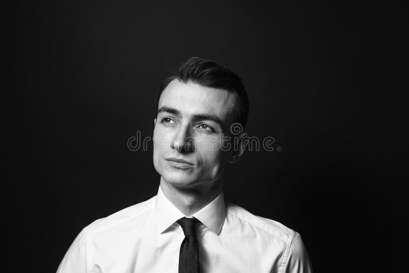 Retrato de un hombre joven en una camisa blanca y un lazo negro fotografía de archivo