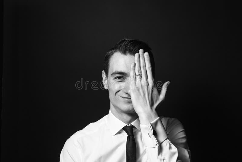 Retrato de un hombre joven en una camisa blanca y un lazo negro, cov de la mano fotografía de archivo