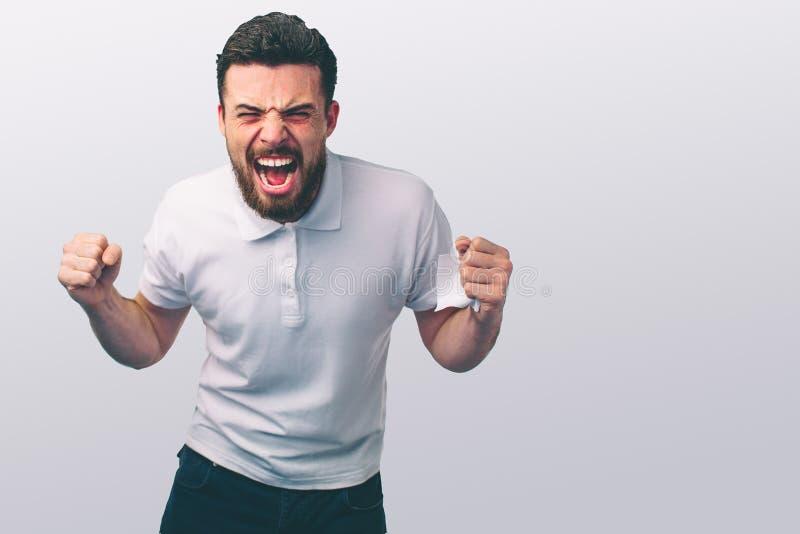 Retrato de un hombre joven enojado Él es aprieta los puños y los gritos Los golpes traviesos del individuo fotos de archivo