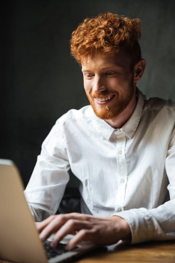 Retrato de un hombre joven feliz que mecanografía en un ordenador portátil fotografía de archivo