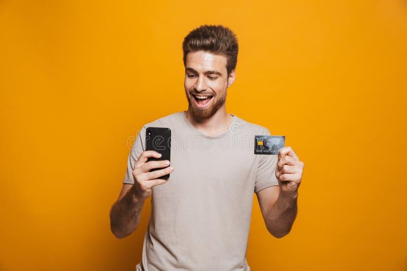 Retrato de un hombre joven feliz que usa el teléfono móvil fotografía de archivo libre de regalías