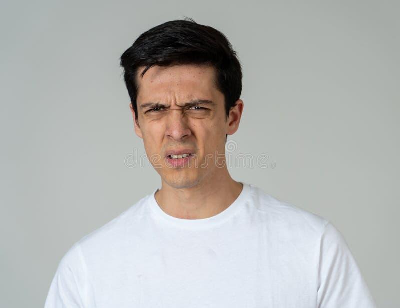 Retrato de un hombre joven hermoso con la cara enojada que parece asqueada Expresiones y emociones humanas imágenes de archivo libres de regalías