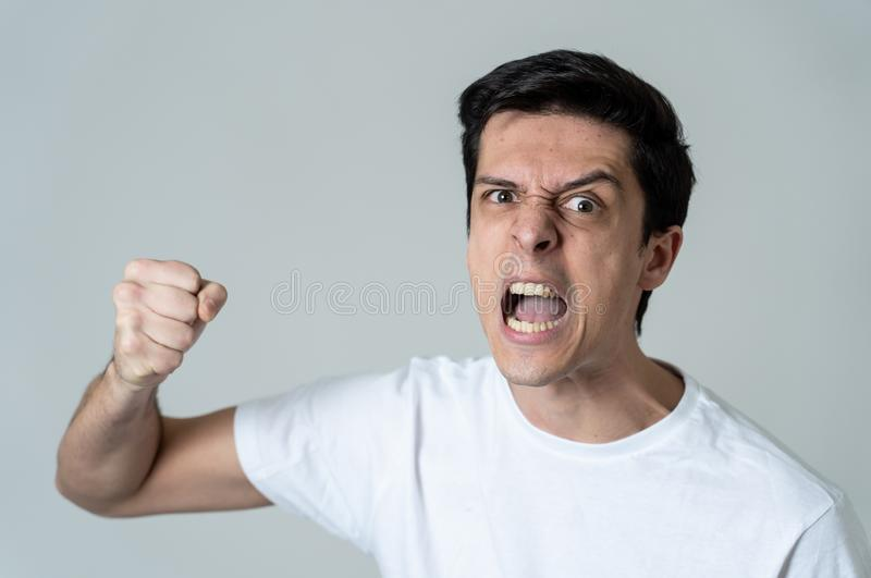 Retrato de un hombre joven hermoso con la cara enojada que parece furiosa Expresiones y emociones humanas fotos de archivo