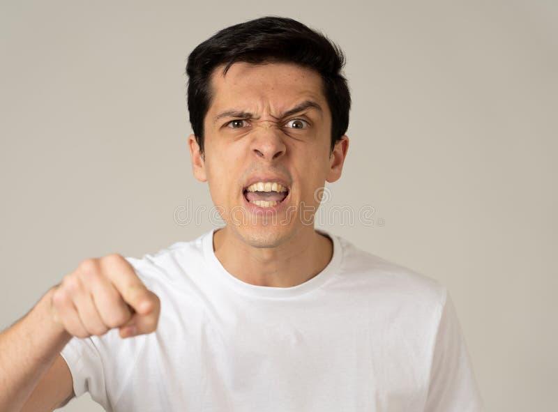 Retrato de un hombre joven hermoso con la cara enojada que parece furiosa Expresiones y emociones humanas fotografía de archivo