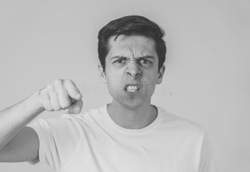 Retrato de un hombre joven hermoso con la cara enojada que parece furiosa Expresiones y emociones humanas imagenes de archivo